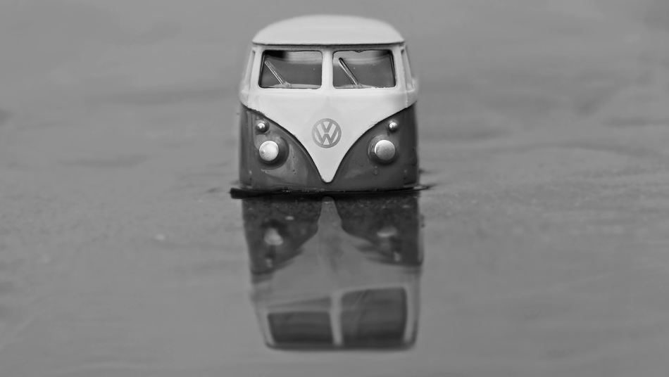 Volkswagen model bus and its reflection on a watery surface