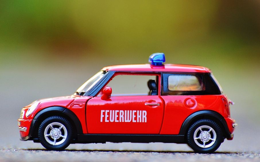 a tiny red service car with blue lights