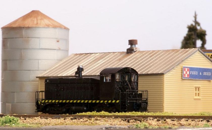 black model train, weathered buildings, green grass