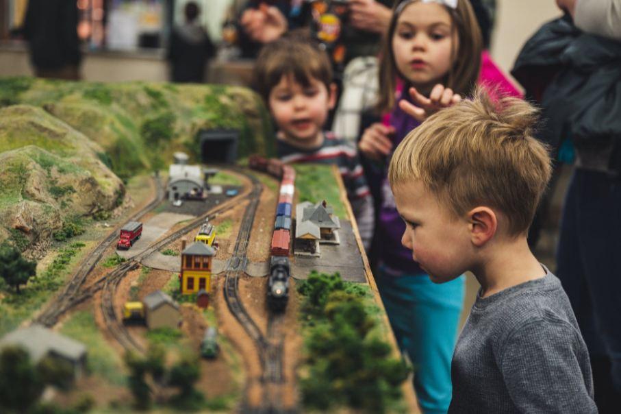 boy-standing-near-miniature-train-toys